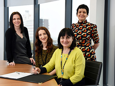 Signing the Memorandum of Understanding between Teesside University and Streetwise Opera. From left - Sarah O'Brien (Programme Leader in School of Computing, Engineering and Digital Technologies),  Ree Collins (Regional Programme Producer, Streetwise Opera), Professor Chrisina Jayne (Dean of the School of Computing, Engineering & Digital Technologies) and Siobhan Fenton (Associate Dean of the School of Computing, Engineering & Digital Technologies).. Link to View the pictures.