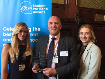 Teesside Law Clinic students, Rachel Simmons, right, Kendal Iley, left, with Andrew Perriman, Senior Law Lecturer, receiving their award at the House of Commons.. Link to Award recognition continues for Law Clinic.