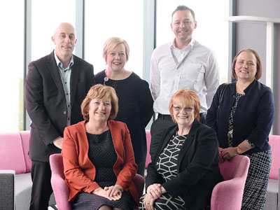 Back row (from left) - Derek Marshall, Chief Workforce Strategist and Planner for Health Education England North East; Gill Hunt, Director of Nursing at South Tees Hospitals NHS Foundation Trust; Scott Godfrey, Nursing Associate Programme Leader; Jan Harris,  Head of Department (Nursing). Front row - Linda Nelson, Associate Dean (Enterprise and Business Engagement), Marion Grieves, Dean of the School of Health & Social Care.. Link to Nursing Associate pilot begins at Teesside University.