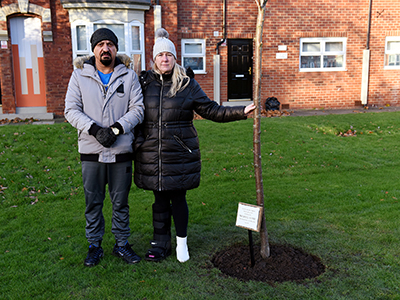 Tan and Michelle Hanif with the memorial tree for Michael. . Link to Lasting legacy for talented student.