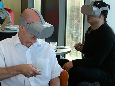Professor Denis Martin (left) trying some of the VR technology. Link to Pioneering research project extended to investigate Covid-19 side effects.
