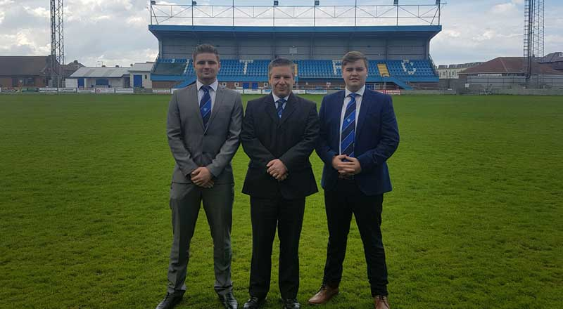 Liam Brown, Mike Edwards, Marketing Director at Whitby Town FC, and James McDonald.. Link to Students flying the flag for Whitby Town FC.