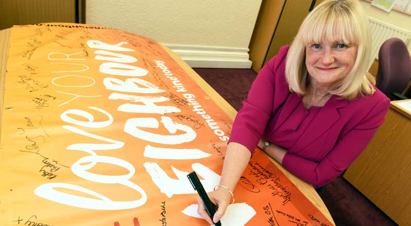 Juliet Amos, Director of Human Resources at Teesside University, signing a banner to support Love your Neighbour.