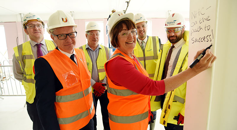 Staff from Teesside University and Wates Construction celebrate the topping out of the National Horizons Centre