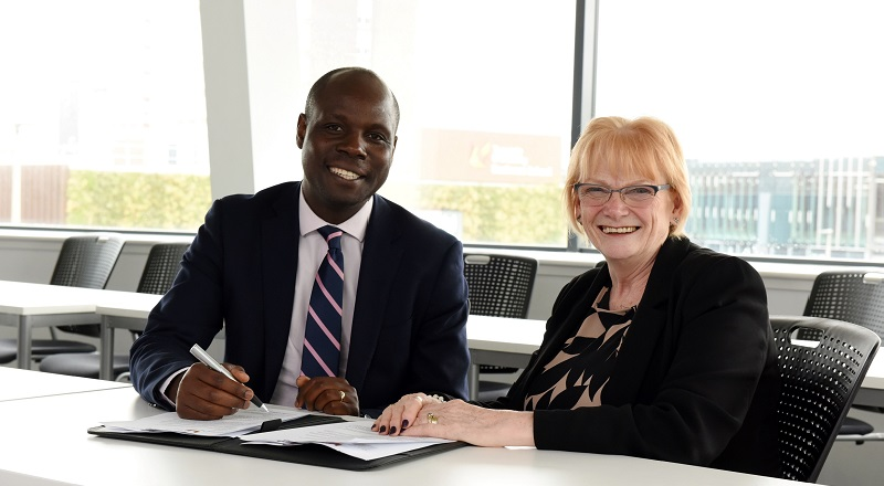 Edward Kunonga signing the memorandum of understanding with Marion Grieves.