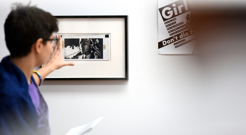 A spectator studying a framed piece of artwork