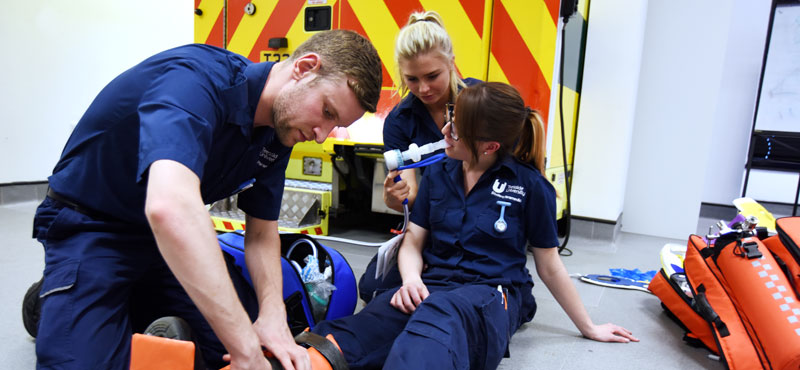 Two students assisting a third with breathing apparatus in the campus' Paramedic suite