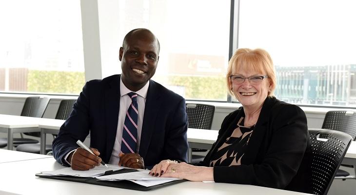 Edward Kunonga signing the memorandum of understanding with Marion Grieves.